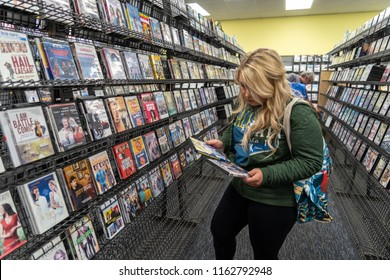 AUGUST 12 2018 - FAIRBANKS ALASKA: Blonde woman customer shops for DVD rentals inside one of the last remaining Blockbuster Video rental stores in the United States