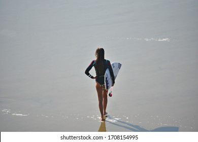 August 12, 2019. Young female surfer on the shoreline of Huntington Beach in Orange County California, USA.