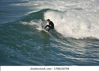 August 12, 2019. Young surfer riding a wave on the shoreline of Huntington Beach in Orange County California, USA.