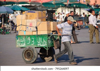 August 15, 2011 - Marrakesh, Morocco - Moroccan man dragging a cart full of boxes with merchandise in the iconic Jemaa el Fna Square. His is going to arrange the stall no. 93 in this famous market.