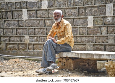 August 15, 2017: An man relaxes on a dilapidated park bench in Kasauli, India. Thousands of people come to the town in summer in search of employment generated by the influx of tourists to the city.