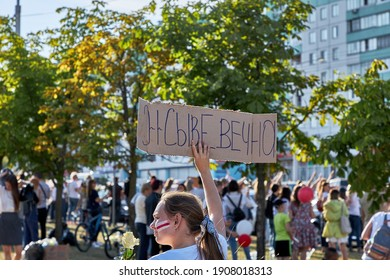 August 15 2020 Minsk Belarus A woman with a painted flag on her face holds a flower and a placard in protest