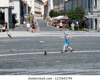 August 16, 2018, Trnava, Slovakia The boy on the square is driving pigeons. Expanded shoulders mimic the flight of a bird.