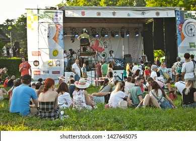 """August 16, 2019. Chernivtsi, Ukraine. Youth, musical ethno festival """"Obnovafest"""". Many people have a rest in nature. Family vacation. People sit on the grass against the background of the scene."""