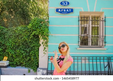 August 17, 2013 Moscow Beautiful blonde girl posing on Arbat Street 53, Moscow. Smiling young woman posing  Happy girl tourist house in which Alexander Pushkin lived is the great Russian poet.