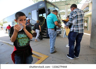 August 17, 2017 - McAllen, Texas, USA - A volunteer with a Catholic Charities' Humanitarian Respite Center helps a group of Central American refugees board a bus to go stay with U.S. family.