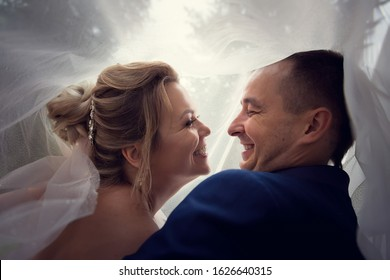 August 17, 2019: close-up and close-up portrait of the bride and groom laughing at each other under a veil.