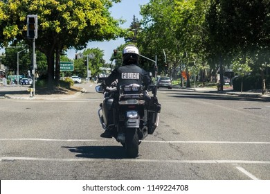 August 2, 2018 Mountain View / CA / USA - A motorcycle police officer on patrol on the streets of south San Francisco bay area; back view