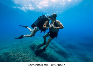 August 20, 2020. Anapa, Russia. Couple of scuba divers kiss underwater in transparent blue sea. Scuba diving in ocean