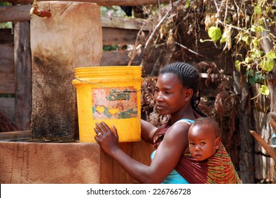 August 2014-Franciscan Mission of Pomerini-Tanzania-Africa-A mother with her ??child while it fills a bucket of drinking water to the public fountain of the Franciscan Mission of Pomerini.