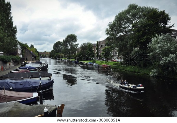 August 2015, Apollobuurt, Amsterdam. The waterscape of the Noorder Amstelkanaal from teh Lyceumbrug under cloudy sky, with a private boat cruising cross the horizon.