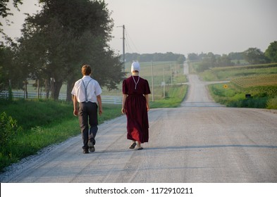 August, 2018 -  An Amish man and woman walk down a gravel road outside of Kalona, Iowa.
