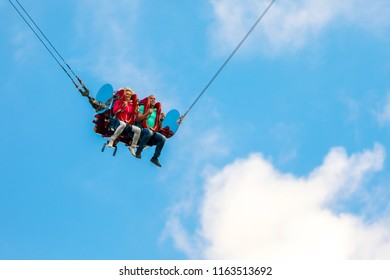 August 2018, Saint Petersburg, Russia. Divo Ostrov amusement park. Happy couple on the catapult slingshot cage closeup with blue sky