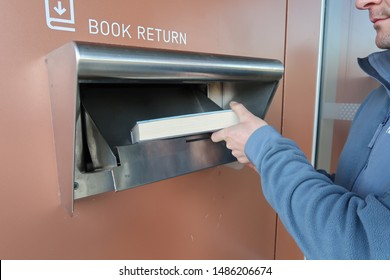 August 2019: Person returning a borrowed library book, placing into the book return chute