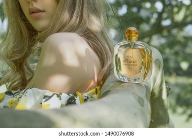 August 2019, Swansea, Wales. Beautiful blonde woman is advertising perfume 'Sun di Gioia' by Giorgio Armani. Product photography of a perfume bottle on a tree branch at dusk.
