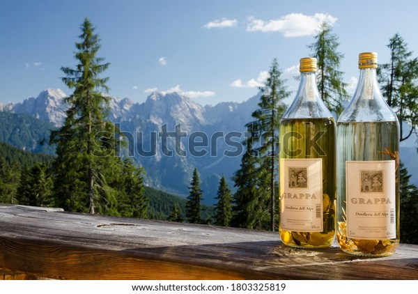 August 2020. Dolomites, Italy. Two bottles of aromatic grappa distilled in a refuge in the Dolomites. In the background the mountains on a sunny day