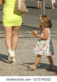 August 21, 2018, Trnava, Slovakia A little girl with a meal in her hand looks at the female feet in a miniskirt, on which to see the emerging varicose veins and cellulite.