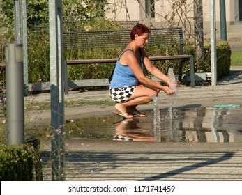 August 21, 2018, Trnava, Slovakia Woman is on a hot summer day refreshes with jets of water from a fountain in a small town park.