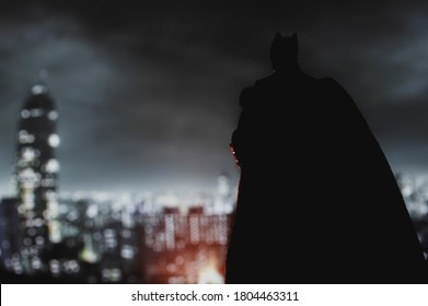 AUGUST 21 2020: Batman from DC Comics looming over Gotham City at night - Mattel action figure