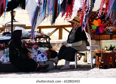 August 21,2012 : Nevsehir / Turkey . (Near Uchisar town in Cappadocia) .Two woman are talking . storekeeper lady is chilling out under shadow with her friend.