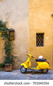 AUGUST 23RD, 2017 - PIENZA, ITALY - Vintage style, Yellow Vespa parked in front of a two toned yellow stone wall taken in the village of Pienza in Tuscany.