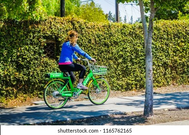 August 26, 2018 Mountain View / CA / USA - Girl riding a Lime bike on a sidewalk in Silicon Valley; Lime is an American transportation rental company that runs bicycle and scooter sharing systems