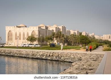 August 27, 2018: Young men jogging near Salam Street Corniche, Abu Dhabi, UAE