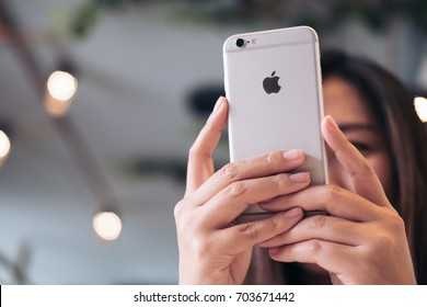 August 27th 2017 : An Asian woman holding , using and looking at smart phone cover her face in modern cafe , Chiang mai Thailand