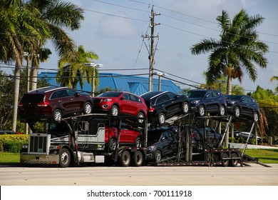AUGUST 3 2016 - DEERFIELD BEACH, FL  A car carrier truck carrying the latest models of new cars is parked on the east side of Powerline Road in the late afternoon sun.