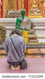 August 3, 2017. A female Buddhist praying kneeling in front of a Buddha statue in the temple of Wat Phrathat Doi Suthep, Chiang Mai, Thailand