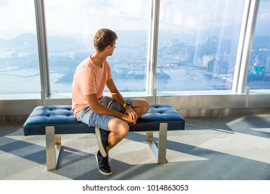 August 30, 2017. Hong Kong. China. Young man sitting on the edge of the skyscraper window in Hong Kong watching the city from above.