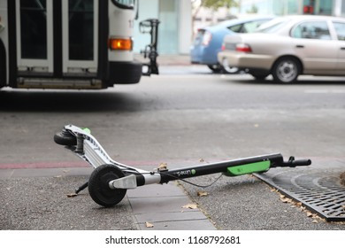 August 30, 2018 - Oakland, California: An abandoned Lime dockless electric scooter of lies on the ground of a street in downtown Oakland.