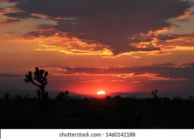 August 4, 2017, Antelope Valley, CA, USA: The summer sun glows red on the horizon in the high desert