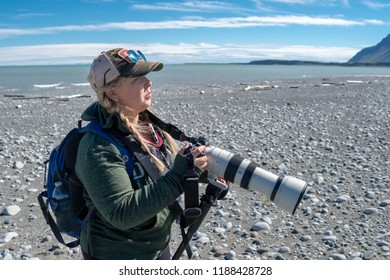 AUGUST 4 2018 - KATMAI ALASKA: Female photographer on a bear viewing excursion in Katmai National Park shows off a large zoom professional DSLR lens