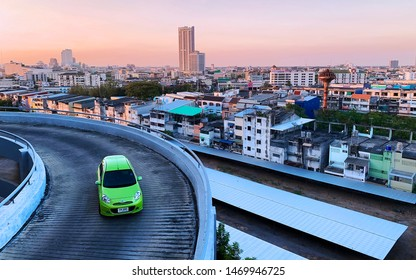 """August 4, 2019 - Hat Yai, Thailand :: A green car """"Nissan March"""" drives on a spiral bridge to exit the parking lot of """"Central Plaza Hat Yai"""" with the panoramic scene of vanilla sky and local city"""