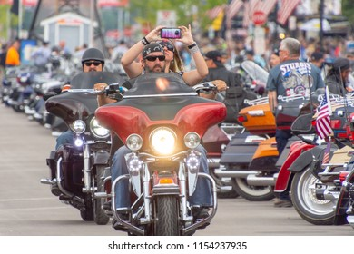 AUGUST 5, 2018, STURGIS, SD: This biker practices safe documentation of the ride down Main Street at the annual Sturgis Motorcycle Rally, in South Dakota. He lets his passenger take the pictures.