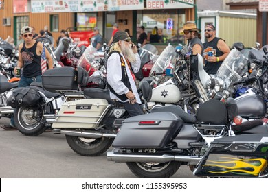 AUGUST 5, 2018, STURGIS, SD: Looking like a character from a recent string of famous pirate films, this gent sits atop the venerable Harley-Davidson Police FLHP Road King, as others look on.