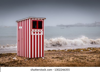 'August bank holiday - an abandoned 'Punch & Judy' booth stands on a deserted beach on a grey and wet August Bank Holiday, at Swanage, Dorset