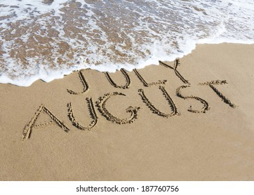 August is coming concept - inscription July and August  written on a sandy beach, the wave is starting to cover the word July.