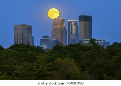 An August Supermoon over Minneapolis, MN Skyline as Lights of the City Turn On