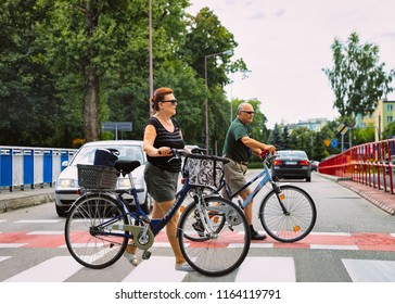 Augustow, Poland - July 29, 2018: Family of senior man and woman on bicycles crossing the street in Warsaw, Poland