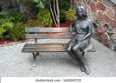 Augustow, Poland - May 2, 2019: Sculpture of a girl with flower, sitting on a bench and waiting for her lover.