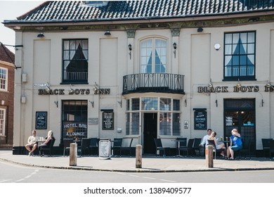 Aulsham, UK - April 21, 2019: People sitting at the outdoor tables of Black Boys Inn pub in Aylsham, a historic market town and civil parish on the River Bure in north Norfolk, England
