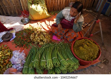AUNG BAN, BURMA - FEB 28, 2015 - Shan women on telphone selling chives and other vegetables at the weekly market near   Inle Lake,  Myanmar (Burma)