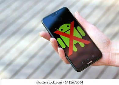 AURA, FINLAND - May 30, 2019: Woman hand holding Huawei smartphone with Android logo and red color cross over it.