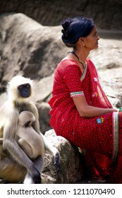 Aurangabad/India - July 2017: An Indian woman in the traditional dress next to mother and baby monkeys in Aurangabad caves, India.