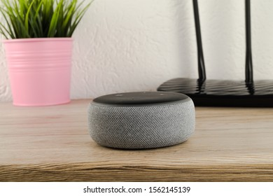 Aurich, Germany - November 09, 2019: Amazon echo dot on a wooden desktop. The echo dot is a hands free voice controlled device that connects to the Alexa voice service.