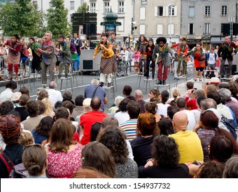 AURILLAC, FRANCE - AUGUST 23: actors perched on bar stools in the middle of the crowd,as part of the Aurillac International Street Theater Festival, Cie Oposito,on august 23, 2013, in Aurillac,France