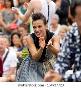 AURILLAC, FRANCE - AUGUST 23:  Cute and smiling actress clapping in the crowd, as part of the Aurillac International Street Theater Festival, Cie Oposito,on august 23, 2013, in Aurillac,France