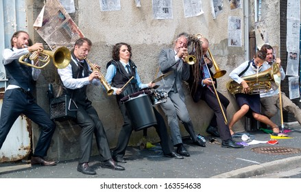 AURILLAC, FRANCE - AUGUST 23: Group of musicians playing against a wall, as part of the Aurillac International Street Theater Festival, cie Rhinofanpharyngite,on august 23, 2013, in Aurillac,France
